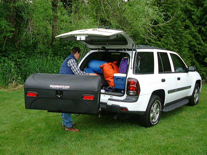 Man packing gear in the back of his vehicle with StowAway Standard Carrier swung out of the way
