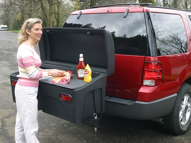 Woman preparing picnic meal on StowAway Standard Carrier with buffet board