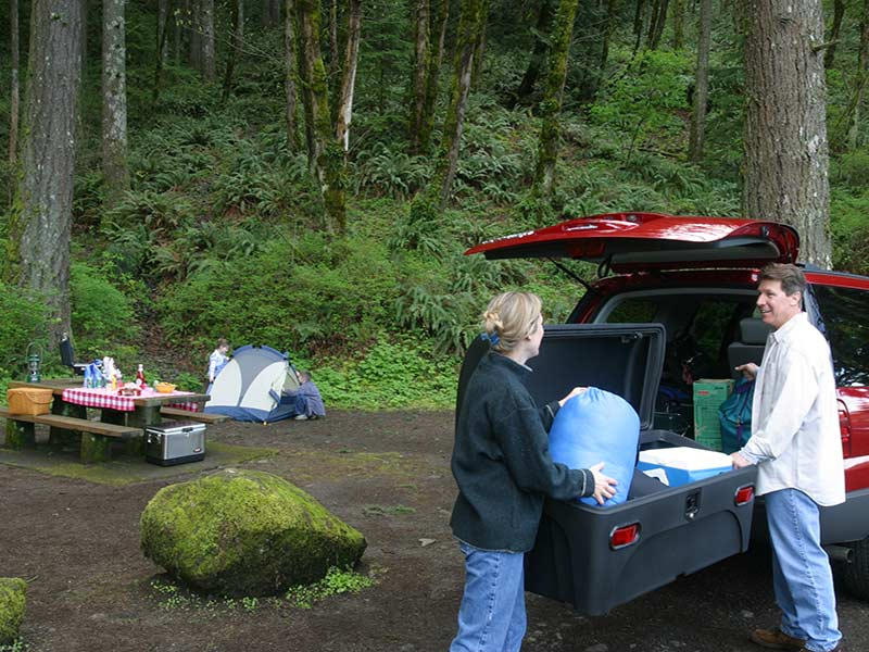 Family unloading their camping gear from the StowAway Standard Carrier