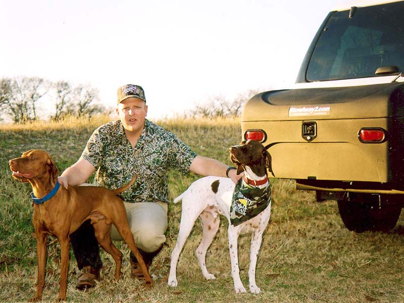 Two hunting dogs with their owner next to StowAway Standard Carrier