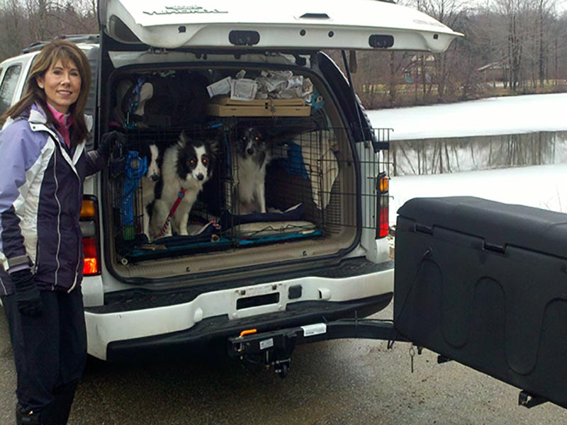 Woman with three dogs in the back of SUV with StowAway MAX Carrier swung out
