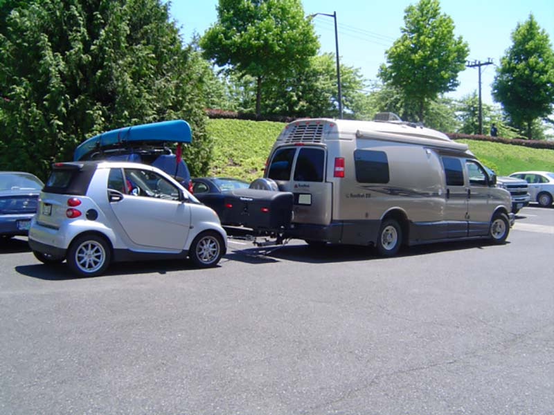 Vehicle with StowAway Standard Carrier and dual hitch towing a smart car