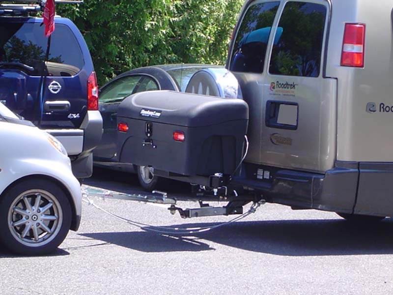 Vehicle with StowAway Standard Carrier and dual hitch towing a smart car close-up