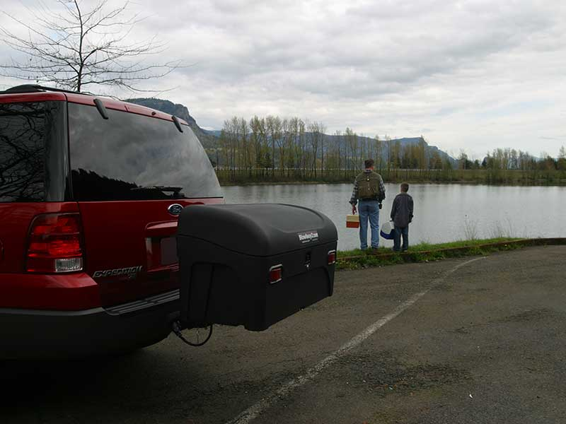 Father and son heading to the river after getting gear from StowAway Standard Carrier