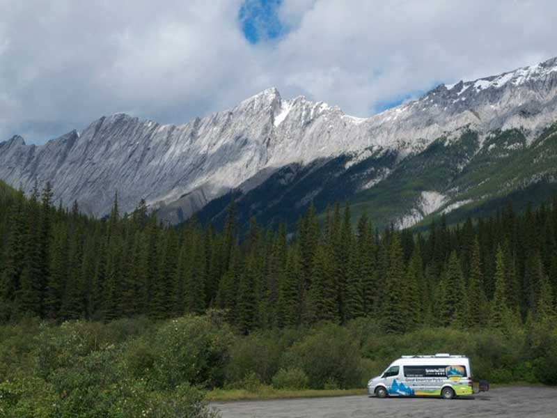 Sprinter tour van parked with view of mountains behind