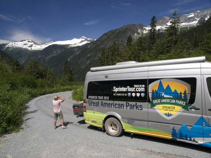 Man gets out of Sprinter tour van to take photo of mountains