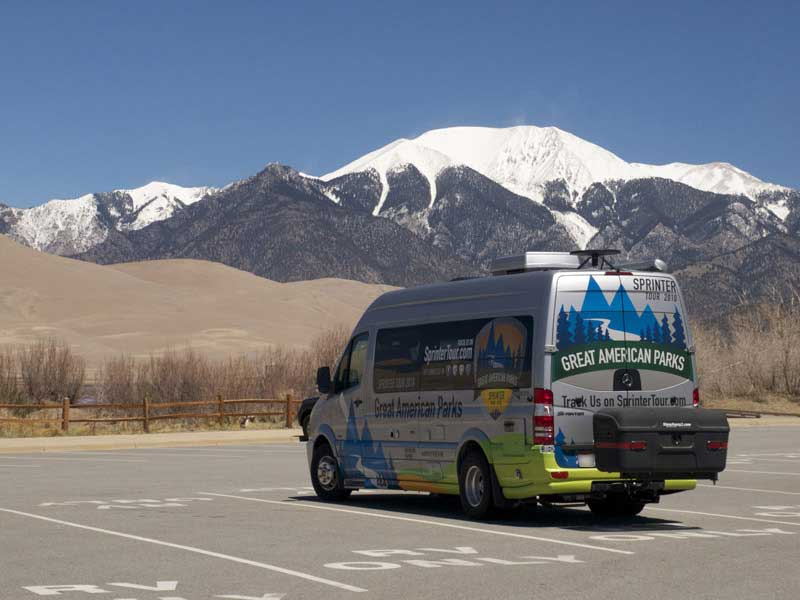 Sprinter tour van with StowAway MAX Carrier in parking lot with view of mountains behind