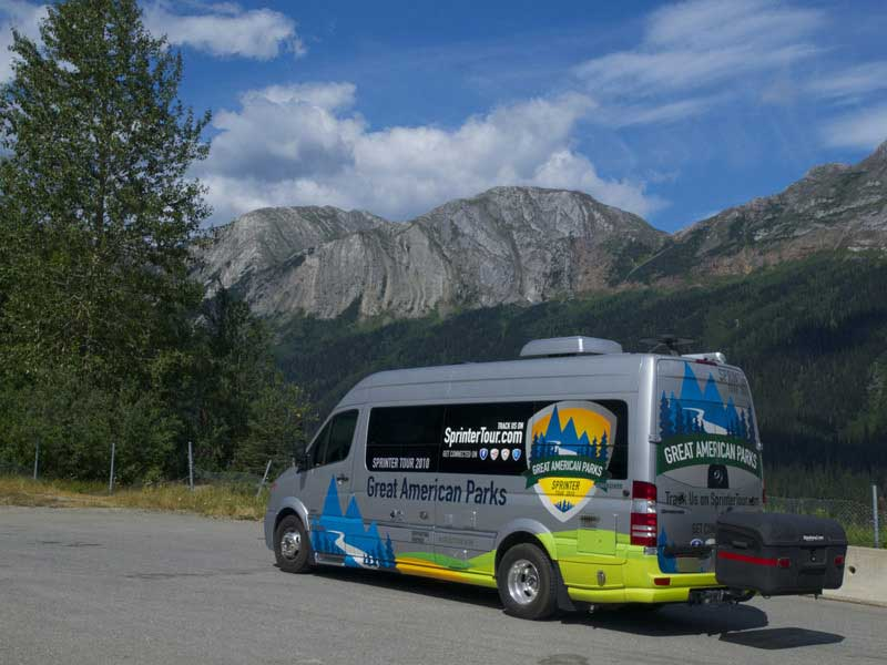 Sprinter tour van with StowAway MAX Carrier parked and view of mountains behind