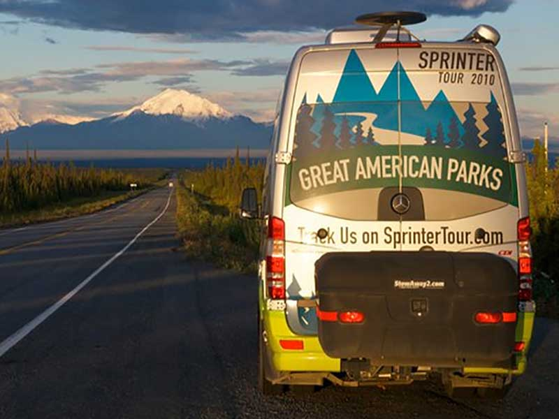 Sprinter tour van with StowAway MAX Carrier on the side of the road with mountain view
