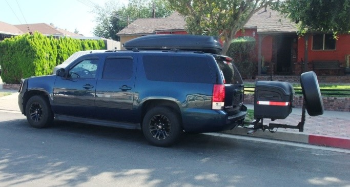 Stowaway cargo carrier on a blue SUV with tire attached