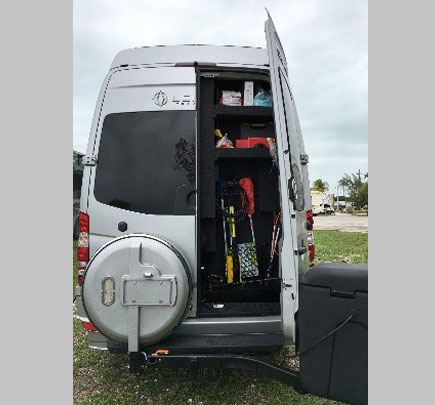 Stowaway box on gray shuttle bus with door opened