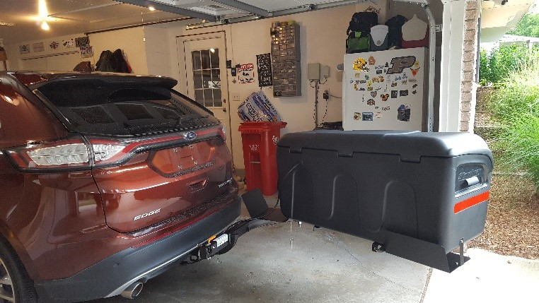 Stowaway cargo carrier on red SUV in garage