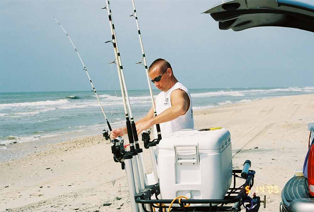 StowAway Cargo Rack with 3-tube fishing rod holder and cooler at the beach