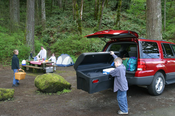 Boy getting something out of StowAway Standard Cargo Carrier on red SUV at a family campsite