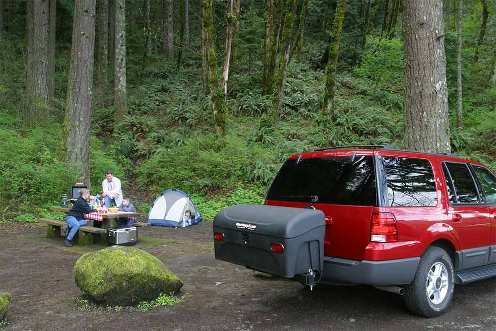 StowAway Standard Cargo Carrier on Ford SUV with family camping in a forest