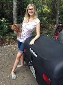 Sophia holding her dog and standing by StowAway Standard Cargo Carrier mounted on Nissan Versa