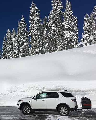 SUV with StowAway MAX Cargo Carrier in front of snow bank