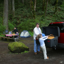 A family unpacking their camping supplies stored in the StowAway Standard Cargo Carrier