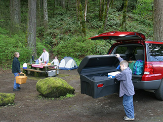 Family at campground; boy unpacking StowAway Standard Cargo Carrier