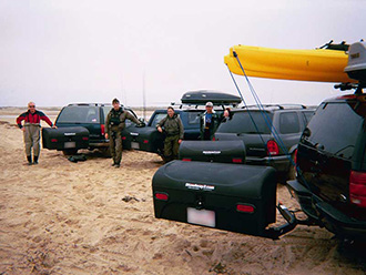 Group of surf fly fisherman with four vehicles, each with StowAway Standard Cargo Carrier swung out