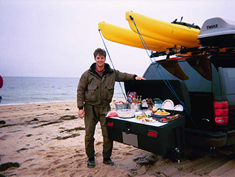 Fisherman on beach standing next to picnic lunch served on StowAway Standard Cargo Carrier with Buffet Board accessories