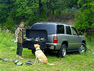 Duck hunter with his dog unloading decoys from StowAway Standard Cargo Carrier on Chevy SUV