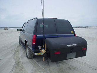 SUV driving on beach with StowAway Standard Cargo Carrier and Fishing Rod Holder attachment