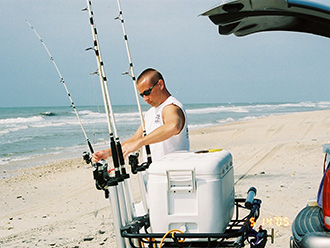 Fisherman at beach with fishing poles in StowAway Surf Fishing Rod Rack