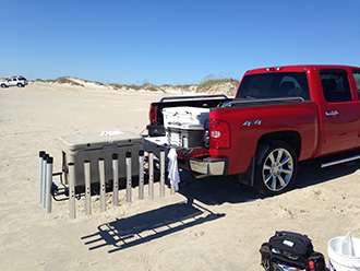 Pickup truck with StowAway Surf Fishing Rod Rack swung out, extra fishing rod holders attached