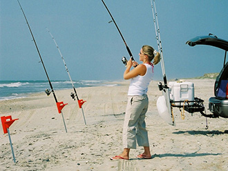 Woman surf fishing near SUV with StowAway Surf Fishing Rod Rack
