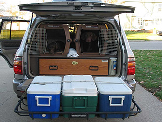 Two dog crates in back of SUV with StowAway Cargo Rack holding three coolers