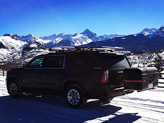 GMC Yukon XL with StowAway MAX Cargo Carrier driving on snowy road in mountains