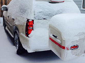 SUV with white StowAway MAX Cargo Carrier covered in snow