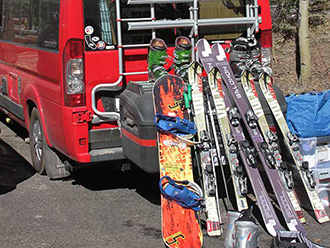 Winnebago Sprinter van with skis and snowboards leaning up against StowAway MAX Cargo Carrier