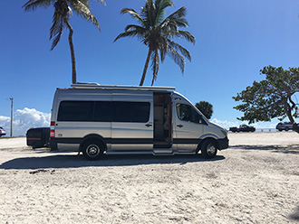 Pleasure-Way Plateau Sprinter van with StowAway MAX Cargo Carrier, parked under palm trees