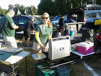 Oregon Ducks fans tailgating with StowAway Hitch Grill Station on pickup truck