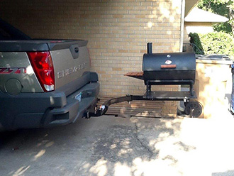 Charcoal grill mounted on StowAway SwingAway frame on Chevy Silverado