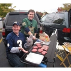 2 guys cooking burgers and brats on their StowAway Hitch Grill Station